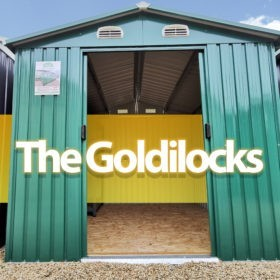 The Goldilocks Shed. It is a picture from a low angle of the front of the shed. The double doors are open and a photoshopped orange bar appears inside the open doors and the words 'THE GOLDILOCKS' are written on this in large font in a shade of off-white.
