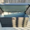The Garden Storage Box from Sheds Direct Ireland. The box has it's hinge open and you can see inside. The unit is the 400L version and it has a grey cushion on top of the open hinge. The cushion is thick. The wall behind is entirely wooden and the sun is rising on the scene, casting long shadows.