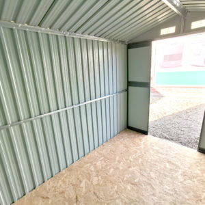 An internal wide angled view of the 6x9 steel shed. It's taken from the corner and the door is visible. The walls are grey, there is green trimmings around the door. The floor is plywood.