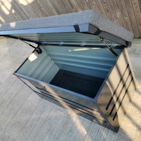 The Garden Storage Box as seen from above. The door is open and the gas-cushioned hinges are visible. The grey cushion on top has support harnesses which are visible because the door is open.