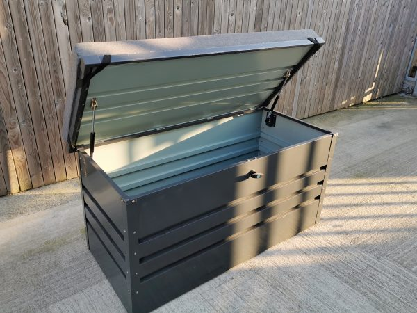 The Patio Storage Box as seen from above. The door is open and the gas-cushioned hinges are visible. The grey cushion on top has support harnesses which are visible because the door is open.
