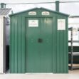 The 6ft x 5ft metal shed in the Sheds Direct Ireland Showroom. There are grey, tall shelves to the right and another shed just out of frame to the left. The 6ft x 5ft Steel Shed is green, with a sign on it that reads 'these doors slide, do not pull'