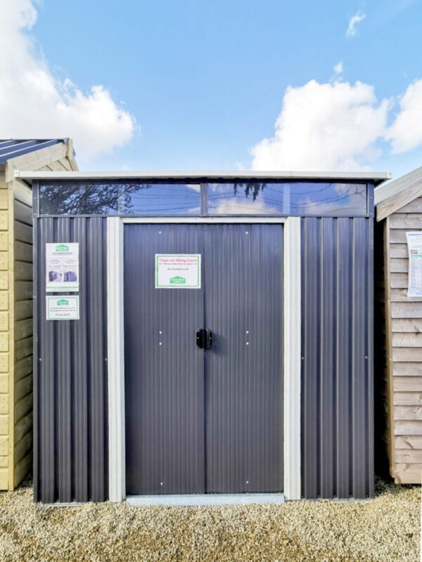 The Steel Pent shed seen from outside, looking straight on. The image is in portrait mode. The sy is blue with sparse clouds above and the ground is a golden-brown pebblestone. The shed is a dark grey, with off-white flashings around the doors. The window above the doors sis reflecting the sky.
