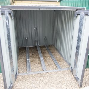 Steel Bike Store with internal tracks for three bikes. The base is a metal frame and there is gravel underneath. The doors are braced and heavy looking.