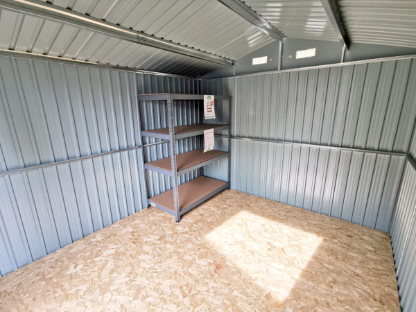 The interior of the 9ft x 10ft Steel Shed. There is a shelving unit in the corner which sits just below the eves of the shed. The floor is plywood and the walls are strengthened by a shiny metal brace. The vents are also visible.