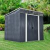 Pent shed displayed in a garden. The skylight is visible and the white frame around the doors can be seen also. The shed itself is a dark grey colour.