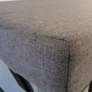 The Garden Storage Box Cushion as seen in grey. It is soft looking and squared out at either end.