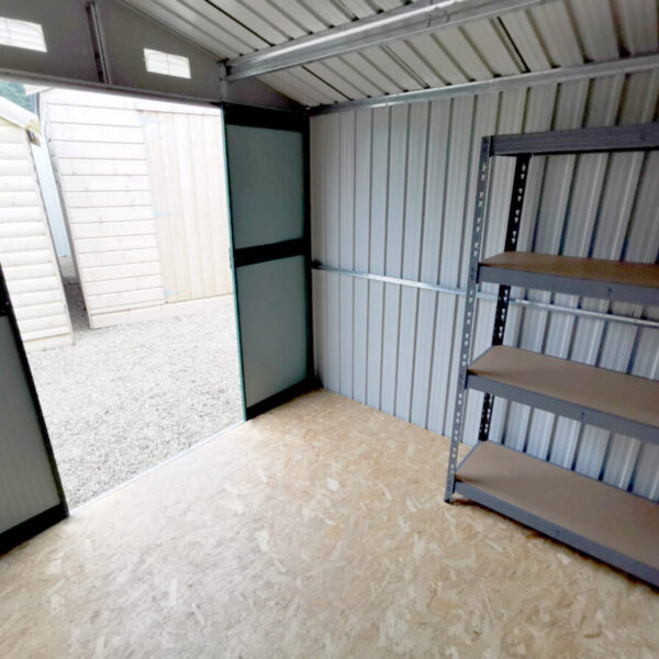 Inside the 7.5ft x 7.5ft Steel Shed. There is a large shelving unit, a plywood floor and a large open door visible. The walls are a pale grey, with vertical slats. Two vents are open above the door too.
