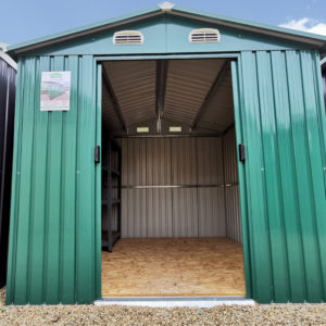 The 7.5ft x 7.5ft Steel Shed in Green. It's seen from a low angle and the doors are open. It has a larbge shevling unit in the far, left corner and the floor is a plywood.