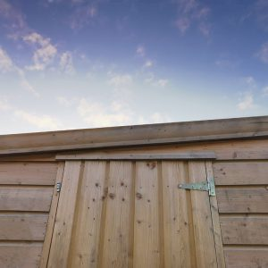 A close up of a wooden cabin shed. The pent roof is sloping down from the right to the left. The top of the wooden door is visible. The sunrise is occurring behind the shed - it is fading from bright blue to dark blue as the sun rises. There is nothing else in the image.