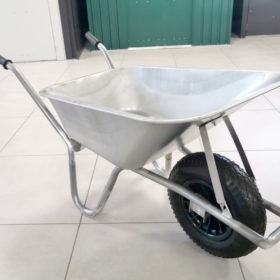 The Steel Wheelbarrow. It's a 90L wheelbarrow and in the picture it's visible in the Sheds Direct Ireland showroom. It's polished grey, with a wheel-guard visible and short handles with black rubber hand-guards on them