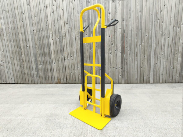 The yellow hand truck with the extendable footplate in the upright position