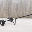 A black trailer dolly with silver, circular ball attachment. The trailer dolly is in a flat position with the handle pointing upwards at a 30 degree angle. It's sitting on a pale paving slab with a wooden wall behind it.