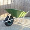 the 90l Wheelbarrow as seen from the front. It's at the front of the Sheds Direct Ireland showroom, against the wooden wall and the long shadows and yellow sun indicate it was taken on an early winter morning.