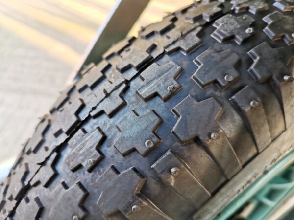 a macro view of the details on the tyre. There are large raised pieces of rubber in the shape on an X, which are deep suggesting they give good traction