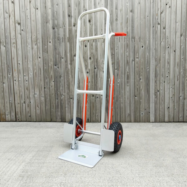 The aluminium hand truck with fold down footplate against a wooden wall