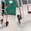 Aluminium Sack Truck with folding footplate. There are two photos stitched together here. One shows the aluminium sack truck in full, with the plate open. The handles are red and the internal wheel parts are also. The second picture shows a close up of the plate closed.