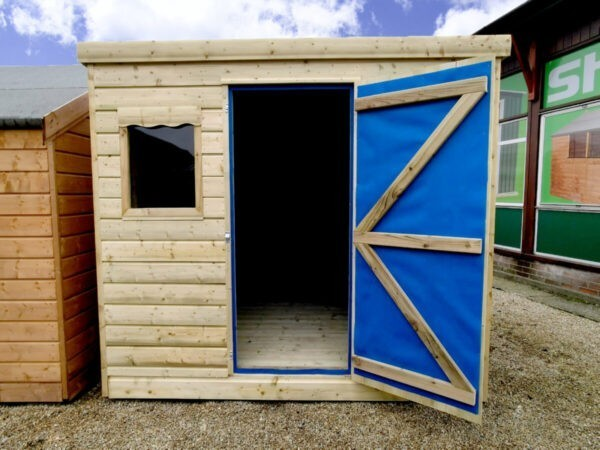 The wooden cabin shed with the door open as seen from the front. The internal wooden floor is visible, but one window is hidden behind the open door. The inside of the door has a blue lining which is for ventilation and temperature control. The shed is on hard gravel and placed beside other sheds. The sky is blue above.