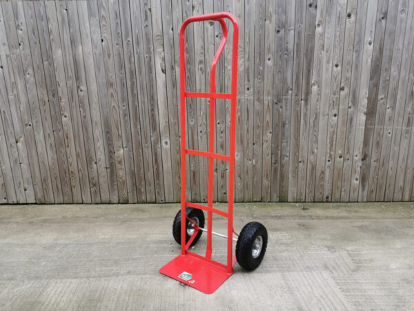 A Red sack truck from Sheds Direct Ireland against a wooden wall. The trolley is large, about 5 foot tall. It has two large outer bars which run from the base to the curved handle at the top. There is an internal bar, which is connected to the external ones by three horizontal bars. They are all red. There is a P shaped handle at the back which curves outward. The wheels at the bottom are thick and black.