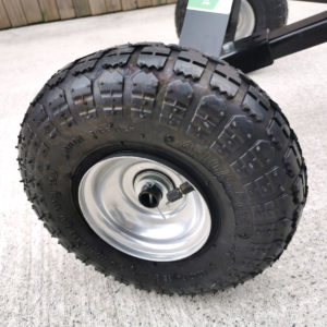 The picture is a close up of the large, black pneumatic tyres of the trailer dolly from sheds direct ireland. They have a steel, internal frame and a pump valvue is visible for inflating (if required)