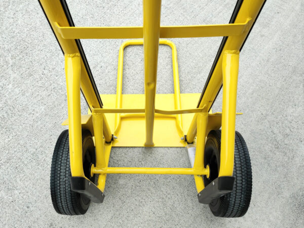 The back of the yellow hand truck as seen from the users view. You can see two wheels, the lifting bar, the extendable footplate