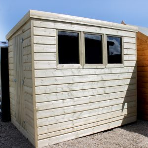 A Wooden Cabin Shed which has been Pressure Treated. The wood is slightly faded in colour because of the pressure treatment. There are three windows on the side of the shed and the door is on a different side to these windows.