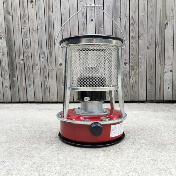 A red camping stove against a wooden wall.