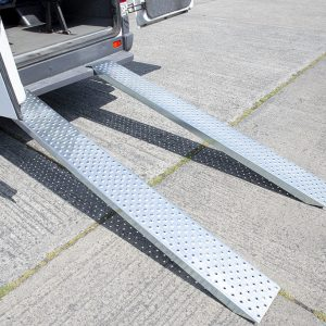 The side view of a loading Ramp from Sheds Direct Ireland attached to a bus