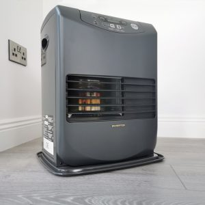 The Inverter 5096 heater in the corner of a white room. The floor is grey hardwood and it appears that the heater is on.