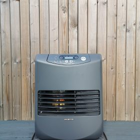 The Inverter 5086 Heater against a wooden backdrop wall. It's at eye level and you can see the heating mechanism through the grate inside.