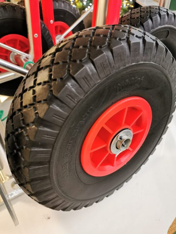The wheel detail on the aluminium sack truck. It's red, with ball bearings and deep groove cuts into the wheel