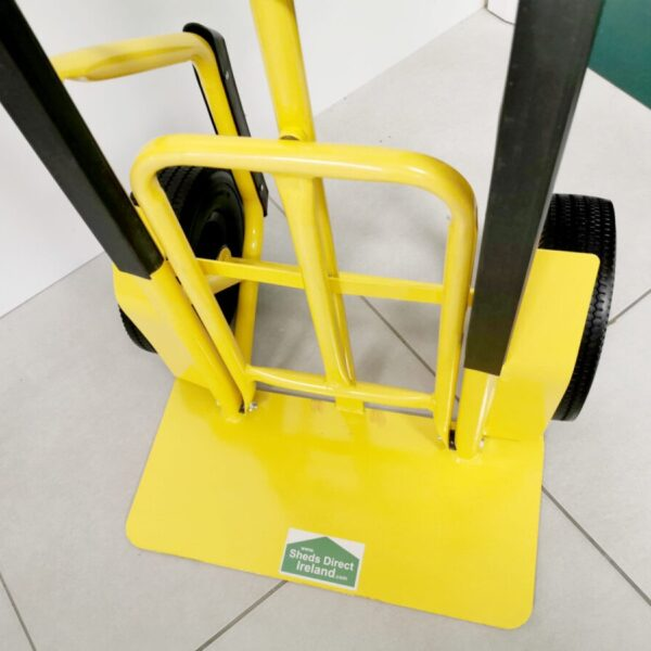 The yellow base plate of the industrial sack truck. The extendable footplate is visible.