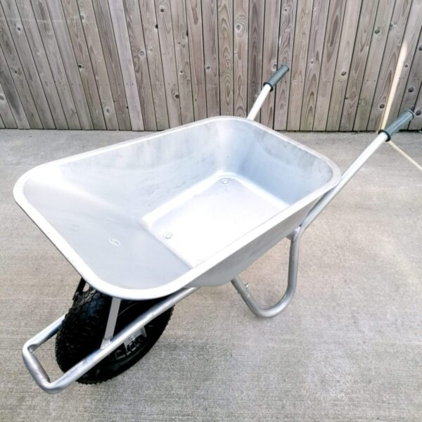 A steel wheelbarrow as seen from a high angle. The inside is bright and semi-shiny.