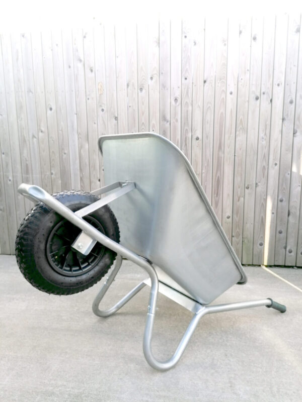 The steel wheelbarrow is lying on its back, the handles and support bars are on the ground and the wheel is raised. It takes up less floor space like this.