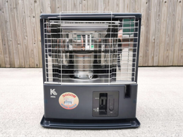 The Tosai / Kero360 Heater against a wooden wall and sitting on a concrete base. It's a large boxy unit, with a black bottom haldf and a metallic upper half. In the metallic half, a silver, tubular burner can be seen. A large yellow sticker below this is emblazoned with a sign that says '3000W'