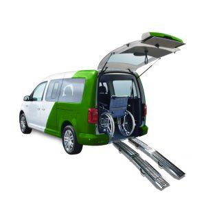 The Folding Ramp connected to a car/van. The car is green and white and it's on a white background. There is a wheelchair in the car and the boot is open.