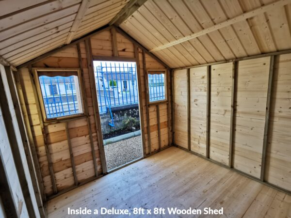 The interior view of an 8ft x 8ft Standard, Wooden Shed. The floor is wooden and the walls have slats connecting them to the roof. The roof peaks and the door is on the short end. The door is open and there are two windows either side of it. You can see some plantlife and a wall in the distance.