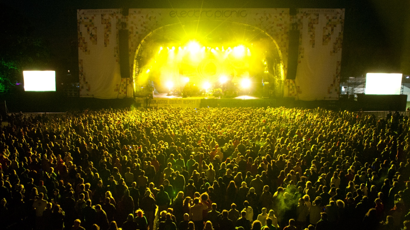 The view from above at Irish Music Festival, Electric Picnic. A band a visible on stage in the distance, but they can not be identified. The crowd are lit by the bright, yellow stage lights. There are thousands in attendance.