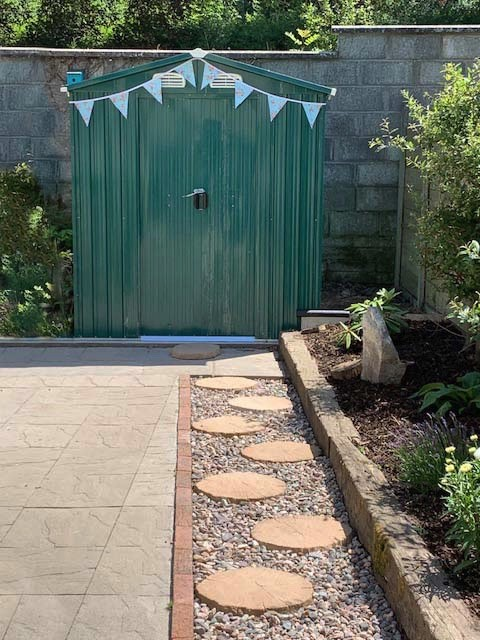 A 6ft wide x 8ft deep steel shed in a customer's garden. They have put pink and pink bunting above the door, it has white polka dots on it. There is a paving slab base to the left of the shed. There is a line of gravel which leads to the door and perfectly circular stone steps are laid into thisn gravel. There is a large fern to the right, foreground also.