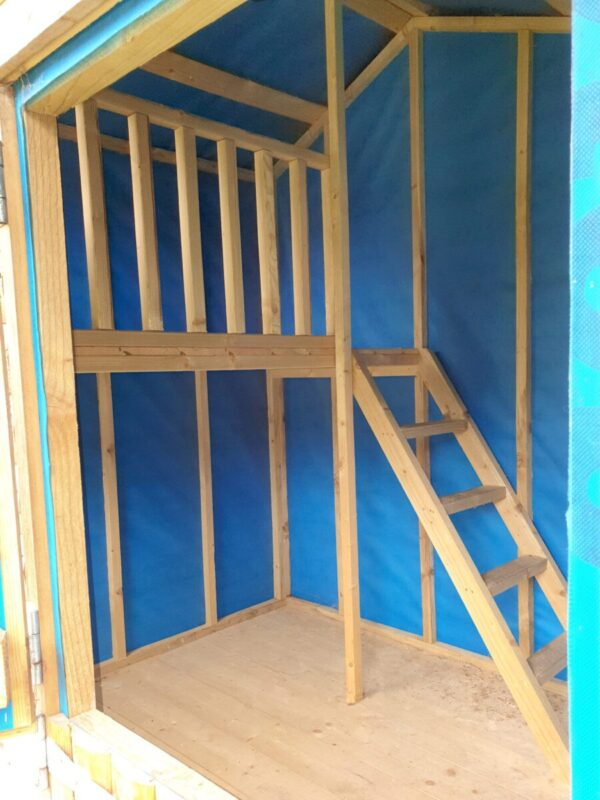 Another interior view of the wooden playhouse, it shows the blue lined walls, the wooden staircase, the hard floor and the landing.