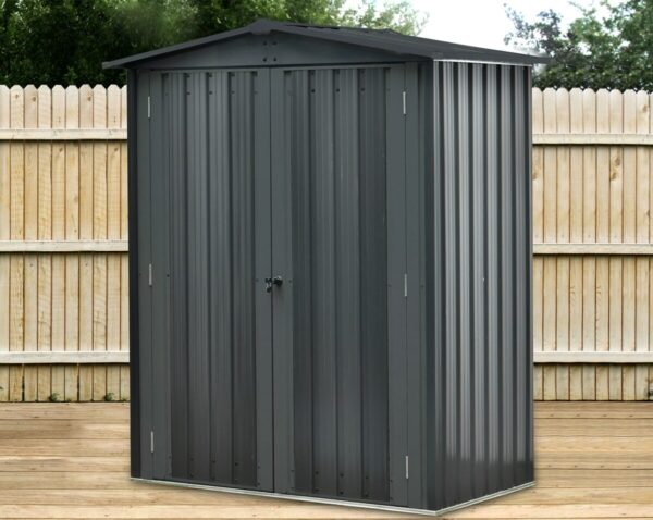 The Balcony Store, a small shed free standing on decking in an Irish Garden. It is black in colour, with a slight grey sheen. There are two doors which are closed and a key in one of the doors. It is mini in size and quite beautifully finished