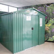 A green, steel shed against a floral wallpaper, in the Sheds Direct Ireland showroom. IIt