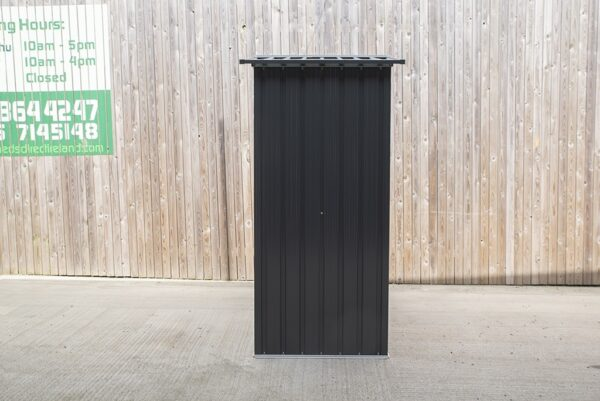 The side view of the small shed. It is about twice as tall as it is wide. It's grey-black and the roof overlaps the body of the shed by about 3 inches either side