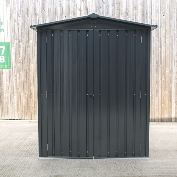 The front view of the small shed. It is grey-black and it has a sloping, peaked roof. The gutters overlap on the shed by about 3 inches either side.