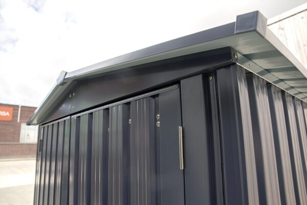 A close up view of the texture of the sheet metal on the shed. The front door is to the left of the frame and the side is to the right. The hinges and gutters are visible