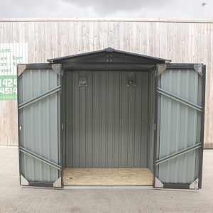 Small shed with the doors open. The sky is grey, and the shed is sitting infront of a large wooden wall. The doors have internal braces that are at 30 degree angles.