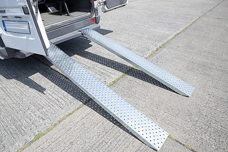 A Solid Loading Ramp from Sheds Direct Ireland. It is connected to the back of a large, white bus. The doors are open and you can see the ramp connects directly to the back of the bus.