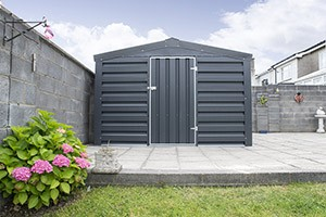 A Heavy Duty PVC Shed from Sheds Direct Ireland - in a very Irish looking garden. There are pink flowers growing to the side of it and a green, lush lawn in front. It is sitting on flat, even grey slabs.