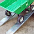 A large, empty Green bucket cart sits on two steel car ramps. The cart is at a 45 degree angle, but it is not moving. The ramps are steel, shiny and have large circular holes in them for grip. The holes are about the size of a 5c coin.