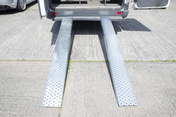 A view of the Steel Ramps as seen from directly behind the bus that they are attached to. They are shiny and clean. There are extruded holes for grip. They support 1,500kg.